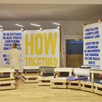 "A semicircular ""agora"" made of wooden crates and plywood walls in a design exhibition."