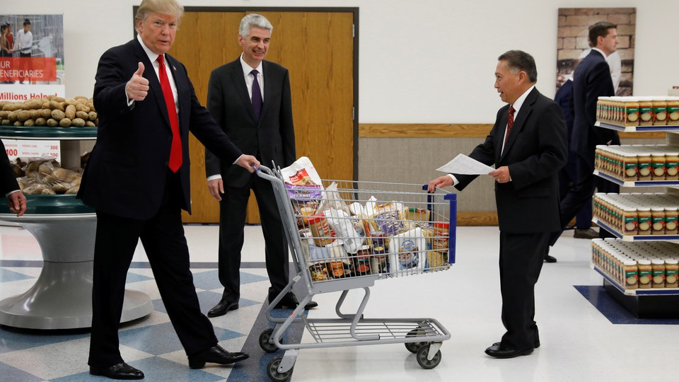 President Donald Trump pushes a shopping cart while giving a thumbs-up.