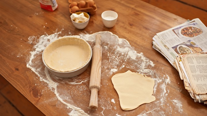 A cookbook next to a rolling pin and flattened dough