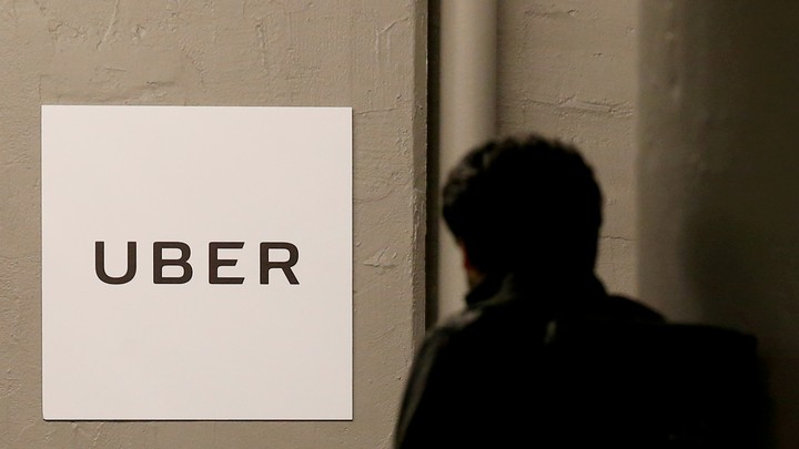 A person walking past a wall with an Uber sign on it