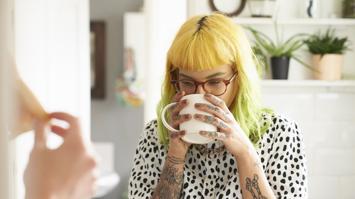 A young woman with dyed hair and tattoos sips a cup of coffee.