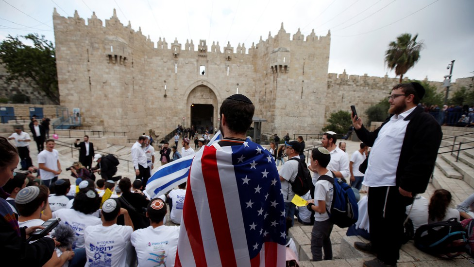 A man wearing an American flag in front of students waving Israeli flags