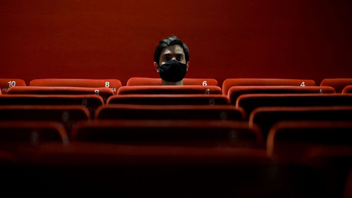 Person sitting alone in a red theater wearing a black mask