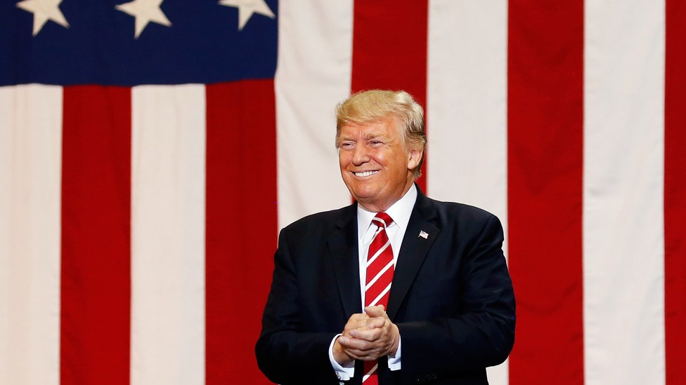 Donald Trump smiles in front of an American flag.