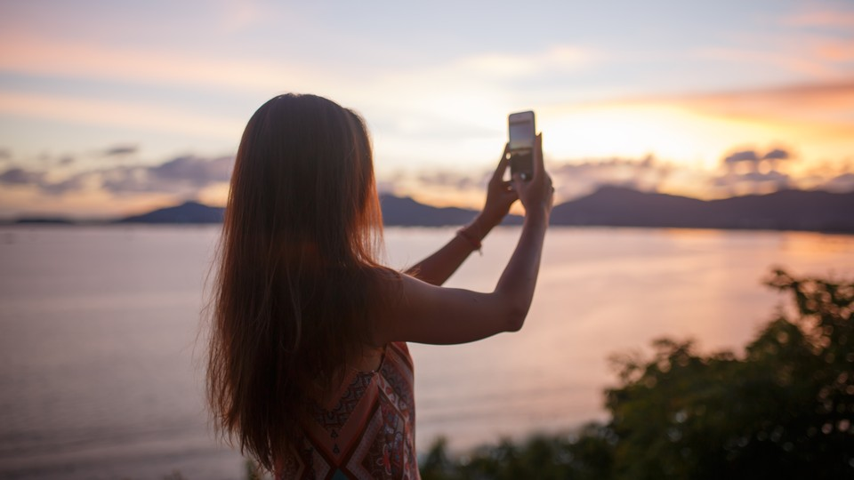 A woman takes a photo of a sunset.