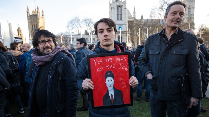 """A protester holds a framed image of Labour leader Jeremy Corbyn and the words """"For The Many Not The Jew."""""""