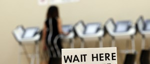 """A sign says """"wait here to vote"""" with a woman visible in the background."""
