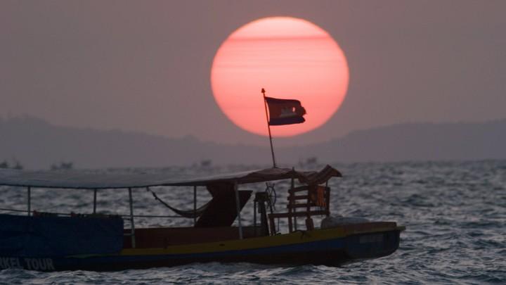 A fishing boat near Sihanoukville flies the Cambodian flag.