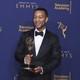John Legend holding his Emmy award