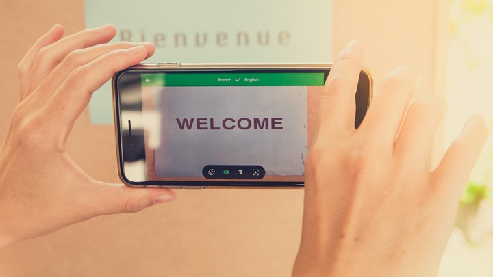 "Hands hold a smartphone in front of a sign saying ""Bienvenue,"" and the smartphone reads ""Welcome."""