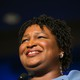 Stacey Abrams looking into the distance. She is smiling and wearing a blue dress.