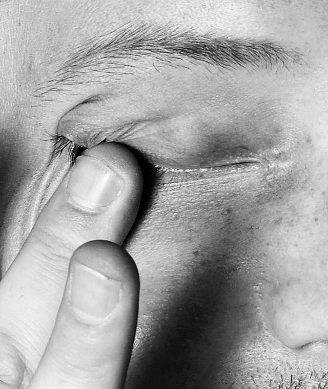 A woman rubs her eye