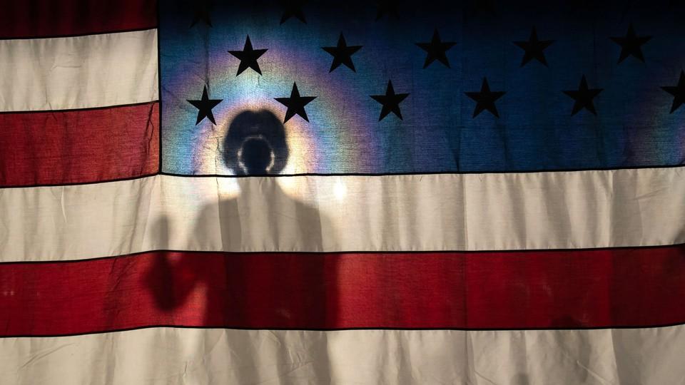 Elizabeth Warren's silhouette is illuminated behind an American flag