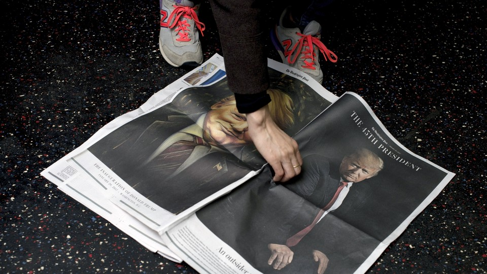 A newspaper bearing Donald Trump's image is picked up off the floor.