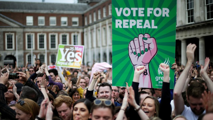 People hold signs celebrating the result of Ireland's abortion referendum in Dublin