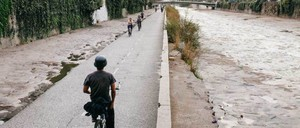 Cyclists ride next to the Mapocho River in Santiago, Chile.