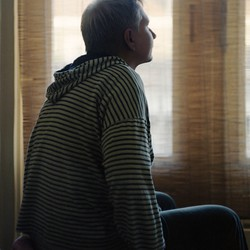 A person sits on top of a bed and gazes toward a window.