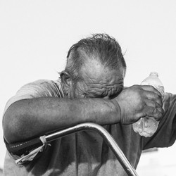 A man holding his head down, grasping a water bottle