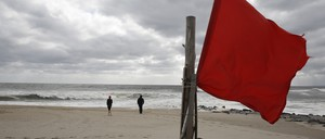 A red flag on the beach warns swimmers of high surf and dangerous currents in the Rockaways in October 2017, five years after the area was ravaged by Sandy.