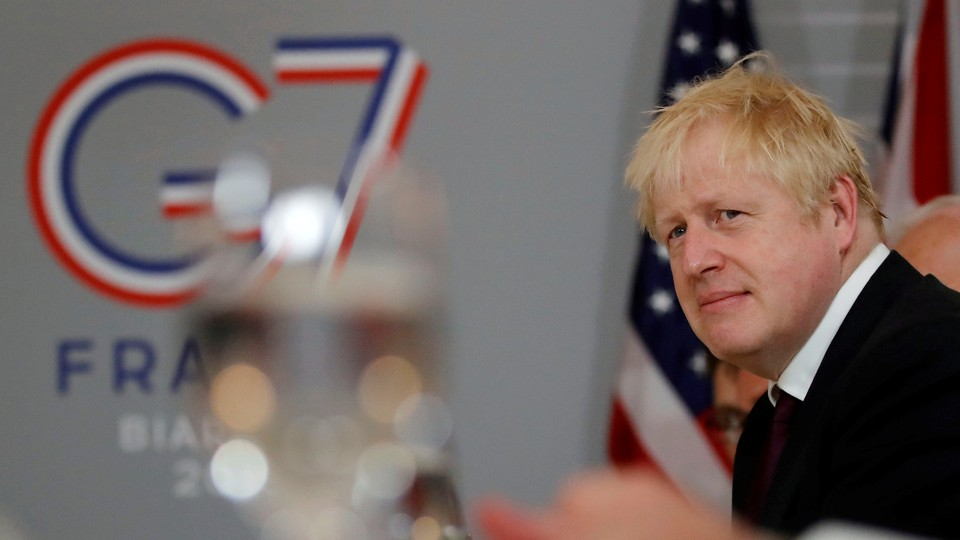 Boris Johnson stands in front of a sign for the G7 in Biarritz.