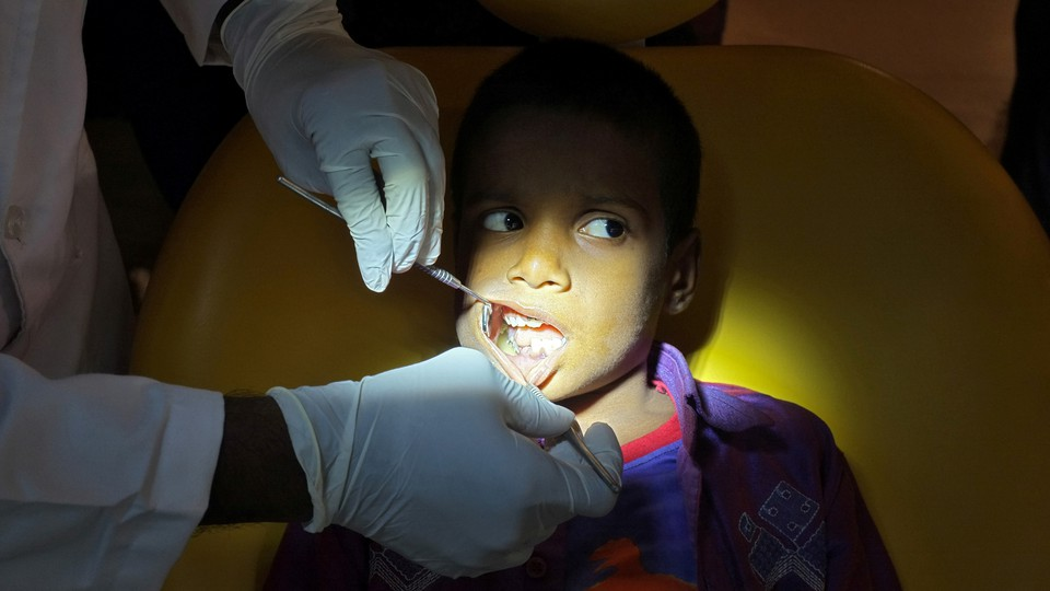 A dentist examines the inside of a young boy's mouth.