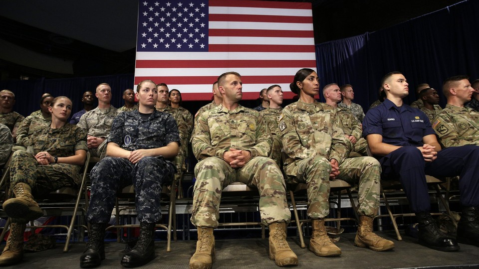 Members of the U.S. military sit in front of an American flag.