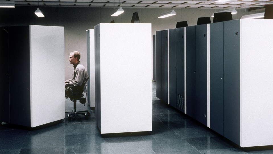 An office worker at a cubicle. He looks bored.