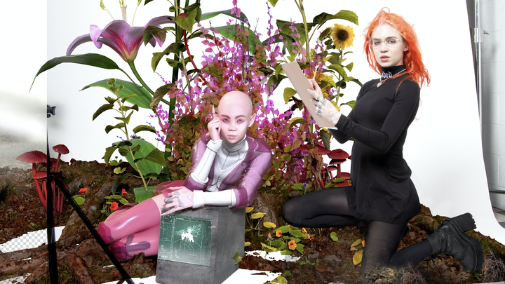 Grimes, in an orange wig, sits amid a field of flowers