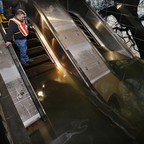 Joseph Leader, the vice president of the New York MTA, inspects a flooded escalator down to a subway platform in the days after Hurricane Sandy.