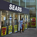 "Customer enters Sears store with ""Store Closing"" signs on windows"