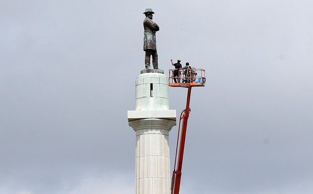 A construction crew in a cherry-picker rise up to dismantle the statue of Confederate General Robert E. Lee in New Orleans