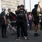 photo: People embrace after a tanker truck drove into protesters on the I-35W bridge on May 31 in Minneapolis.
