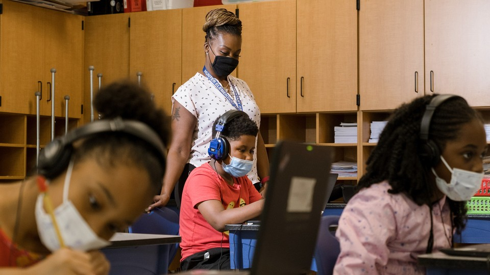 Tonette McQueen helps Zion Graham, 8, with a summer school assignment at Hunter Elementary in Greensboro, North Carolina., July 19, 2021.
