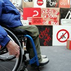 A wheelchair user is pictured in front of protest signs about accessibility.