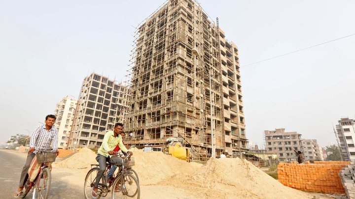 Men ride their bicycles past residential buildings under construction on the outskirts of Kolkata, India, on February 1, 2017.
