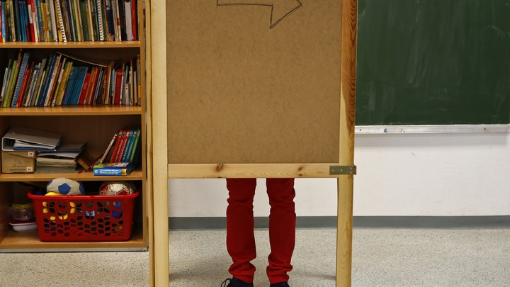 A pair of legs are visible behind a wooden corkboard in a classroom.