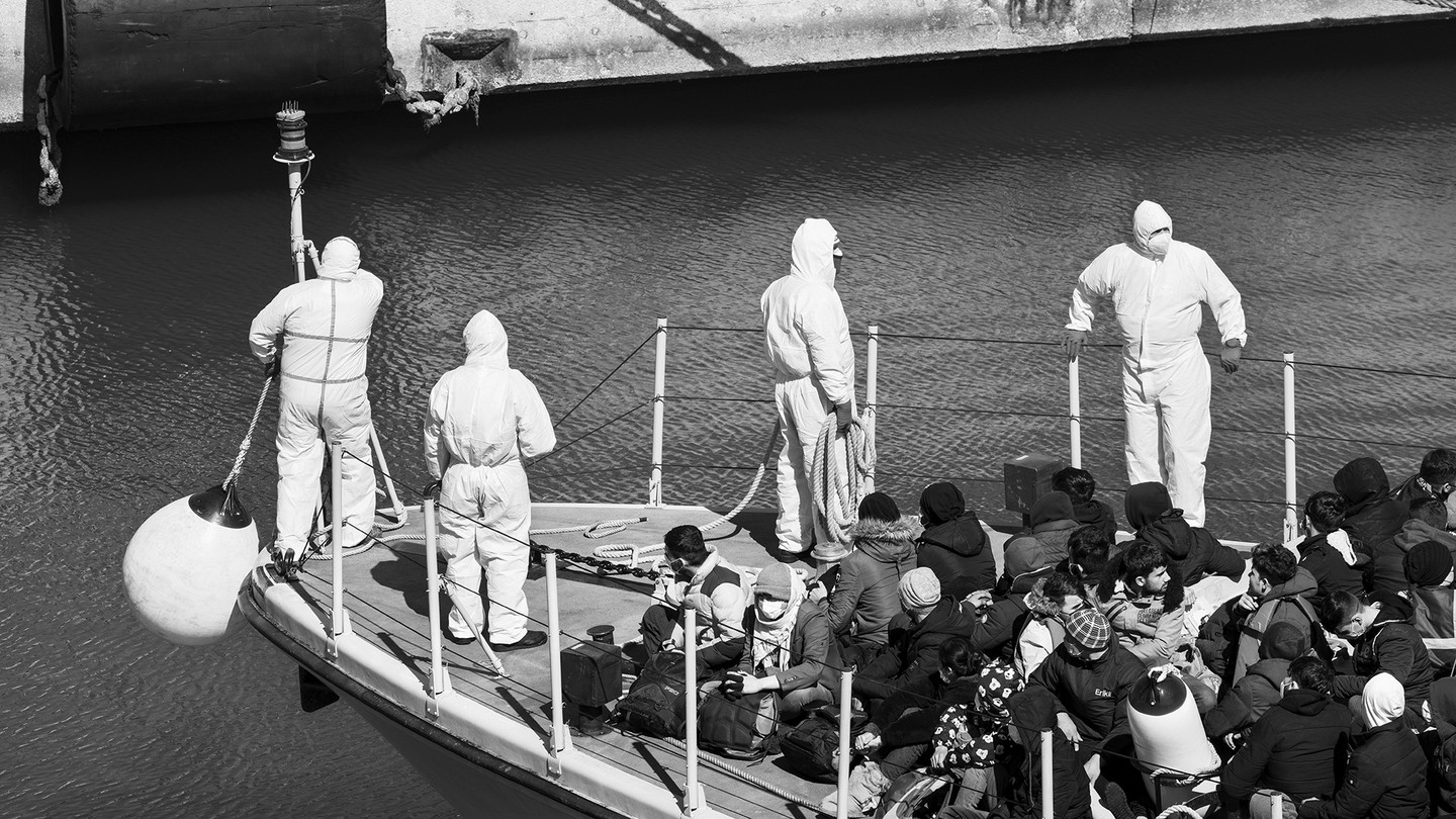 Italian law enforcement and a group of migrants gathered on the prow of a ship