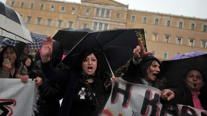 Suspended Finance Ministry janitors protest outside the Greek Parliament in 2013.