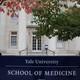A man in scrubs walks outside the Yale School of Medicine.