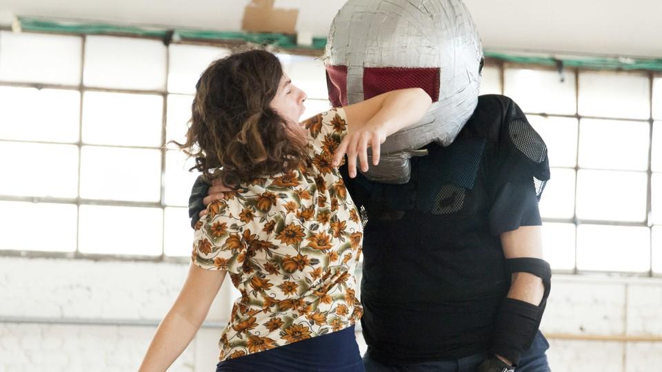 A woman elbows away an assailant in a self-defense class.