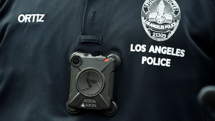 A square black camera on a police officer's black uniform shirt