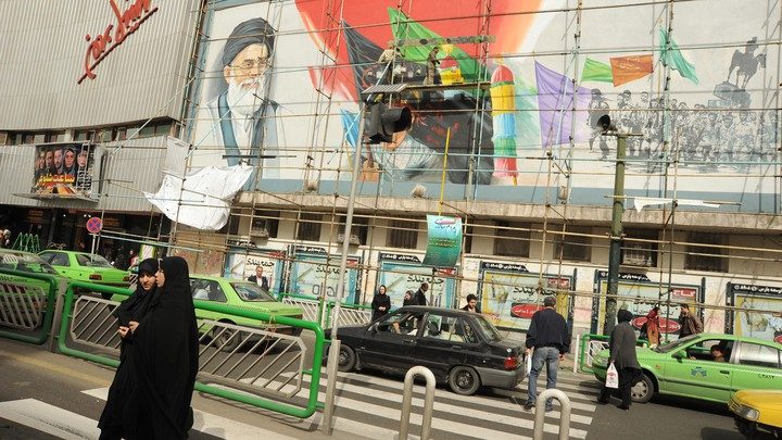 Young women fully covered in black chadors walk in front of a mural of Iran's leader Ayatollah Seyyed Ali Khamenei being refurbished on the corner of Revolution Square on March 1, 2012 in Tehran, Iran.