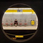 photo: A commuter, wearing a protective face mask, waits on the platform for a Milan Metro subway train in Milan, Italy,
