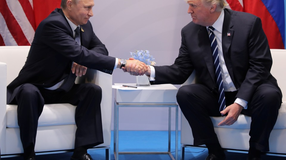 President Trump (right) and President Putin (left) sit on chairs and shake hands while answering questions during a bilateral meeting of the G20 Summit.