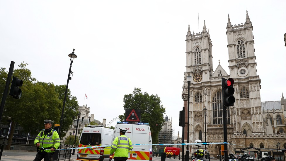 Police officers stand at a cordon after a car crashed outside the Houses of Parliament in Westminster on August 14, 2018.