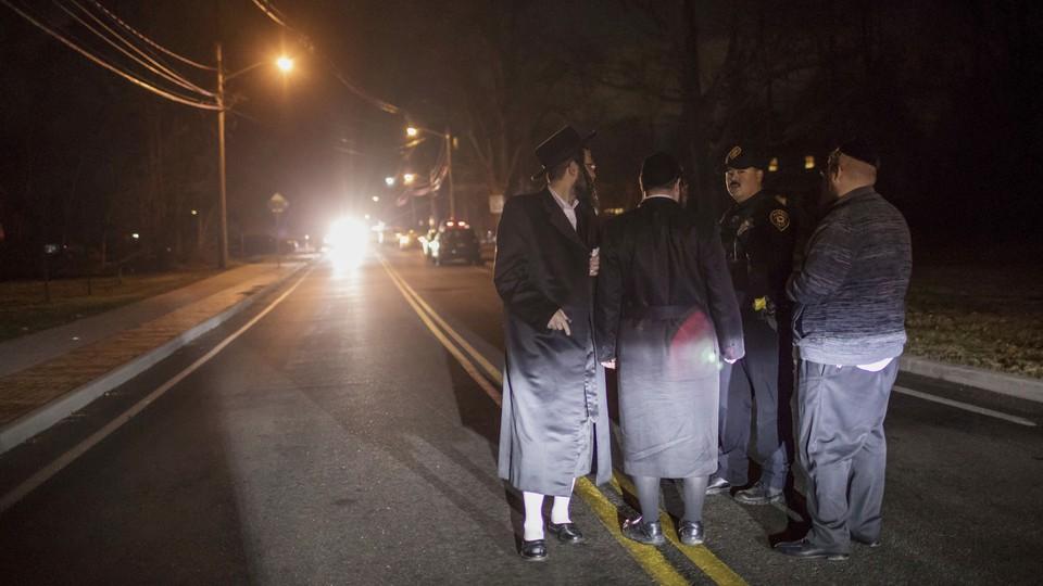 Orthodox Jews near the scene of a late-Saturday stabbing