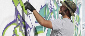 Graffitti artist Anthony Arias works on a mural during Art Basel Miami Beach in 2014.