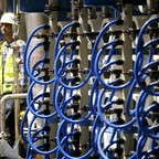 Rows of machinery with long blue tubes and pipes seen at a water desalination plant.