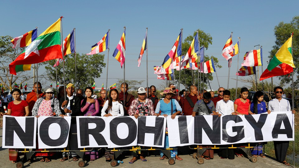 """Buddhist monks and Yangon residents protest the arrival of an aid ship bringing humanitarian supplies to Rohingya Muslims in Yangon by holding a sign that reads """"No Rohingya"""" in February 2017."""