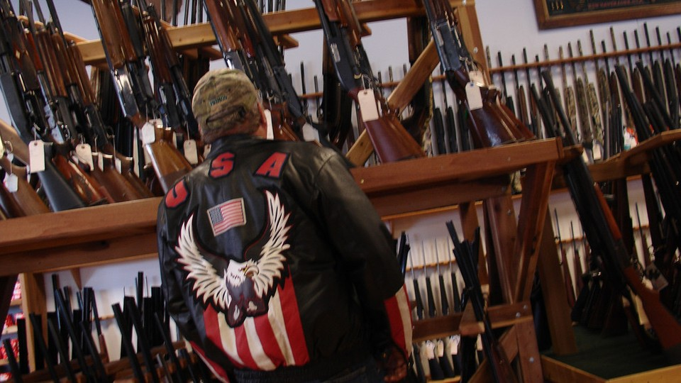 A man in a jacket featuring a bald eagle and the American flag stands in front a collection of rifles.